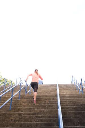 een atletische vrouw sprint een trap buiten op als onderdeel van een intensieve intervaltraining