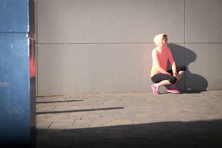 afbeelding van een vrouwelijke atleet die zich uitstrekt en herstelt na een wandeling in een stedelijke omgeving
