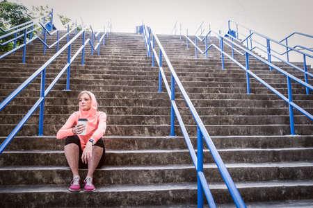 afbeelding van een vrouwelijke atleet zittend op trappen en met een post workout herstel drankje