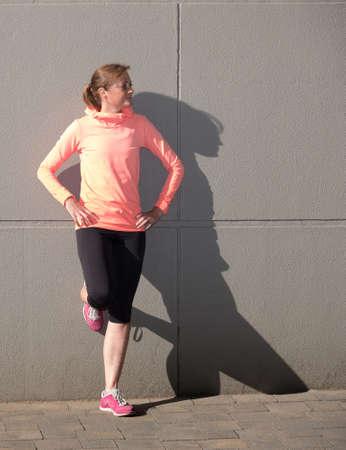 atletische vrouw in sportkleding poseren tegen een muur die een schaduw werpt