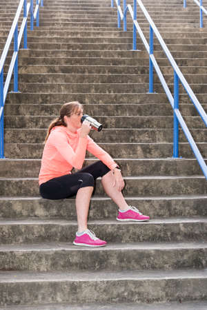image of a female athlete sitting on stairs and having a post workout recovery drink Stockfoto