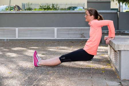 afbeelding van een vrouwelijke atleet doet een triceps dip in een stedelijke omgeving Stockfoto