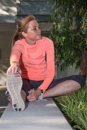 image of a female athlete stretching and recovering after a waork out in an urban setting