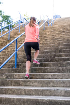 an athletic female sprinting up a flight of outdoor stairs as part of a high intesity interval workout Stockfoto