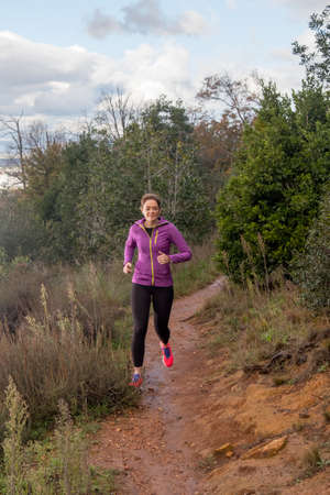 thirty something ginger female trail runner running on a single track in cape town on a stormy winters day