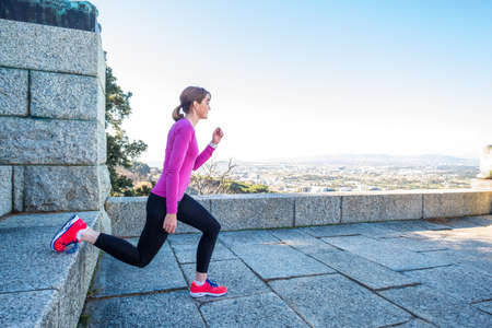 Image of an active female doing a lunge on a stone wall outdoors on a sunny day