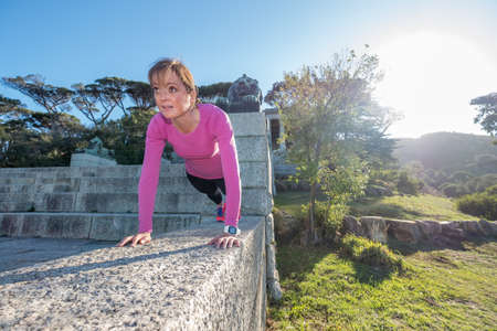 Image of an active female doing a plank on a stone wall outdoors on a sunny day