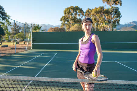 female tennis player standing at the net of the court Stockfoto - 105527955
