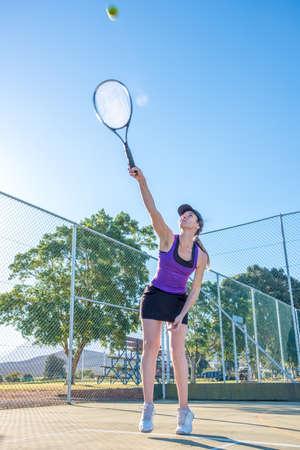 female tennis player serving during a tennis match