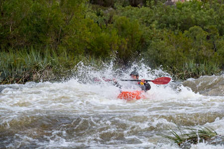 Image of a kayaker in an orange kayak padding through some white water rapids on a river in Du Toits Kloof near Cape Town South Africa