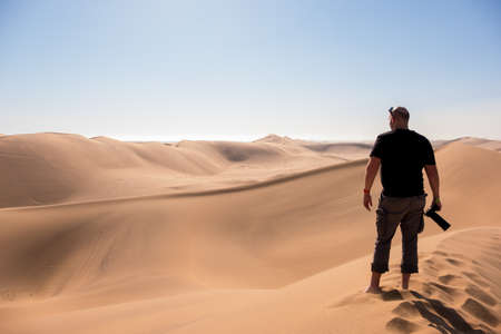 Vibrant Image of a photographer stood on Dune 7 with the surrounding sand dunes near Swakopmund, Namibia, Africa, in the background Stockfoto - 106119651