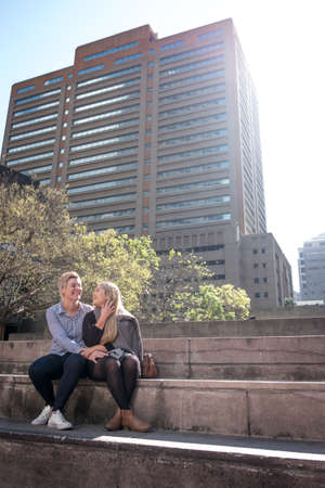 two lesbian gay women in their twenties enbrace in a city landscape in Cape Town, South Africa Stockfoto - 107323097