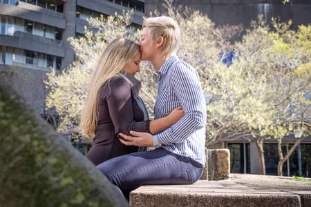 two lesbian gay women in their twenties enbrace in a city landscape in Cape Town, South Africa