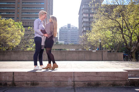two lesbian gay women in their twenties enbrace in a city landscape in Cape Town, South Africa Stockfoto - 107340973