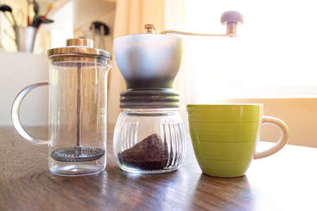 plunger filter coffee being prepared at home on a vintage jug with green cup