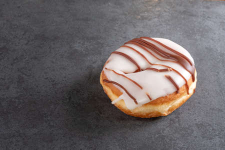 white iced ring doughnut on a slate background
