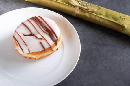 white iced ring doughnut on a white plate with napkin and slate background