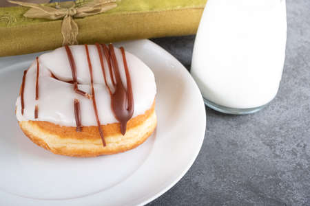 white iced ring doughnut on a white plate with milk, a napkin and slate background Stockfoto