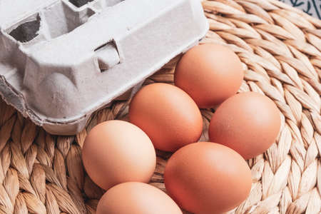 eggs and an egg box on a woven mat background Stockfoto
