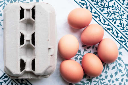 eggs and an egg box on a blue and white table cloth background