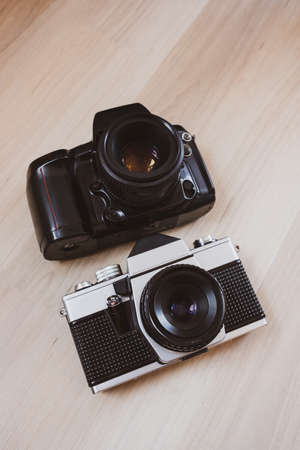 two vintage 35mm film cameras on a light wooden background