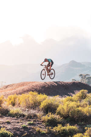 backlit image of a mountain biker jumping on a dirt track mound with a mountain range behind him