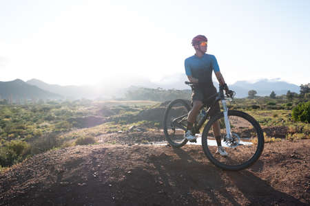 backlit image of a mountain biker and his bike on top of a mound with a mountain range in the distance Stockfoto