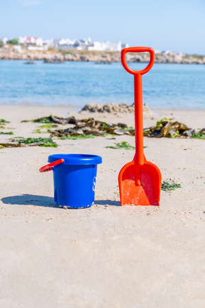 red spade and blue bucket on a sandy beach on a summers day