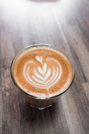 latte coffee with attractive pattern in a glass cup on a wooden table