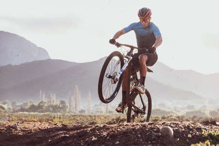 mountain biker pulling a wheelie on a sunny day