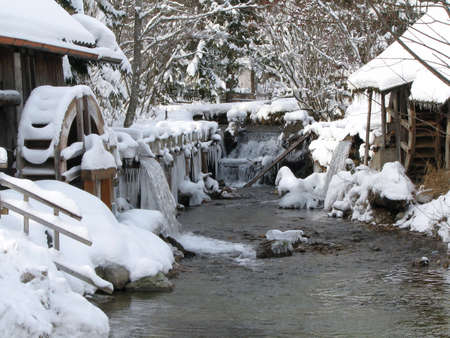 An icy creek on a chilly winter day with snowy trees and a water mill in the background