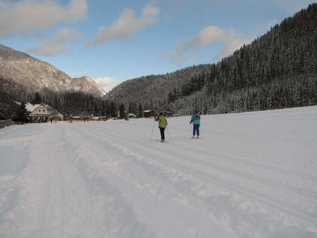Beautiful winter landscape showing a cross-country ski run with people skiing photo