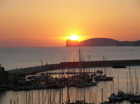 A becautiful sunset over the harbour in Alghero (Italy) Stock Photo