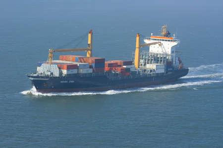 containership: Containership with containers leaving the harbor