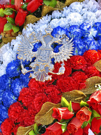 doubleheaded: Wreath of artificial roses in tricolor and emblem of Russian coat of arms in form of double-headed eagle. Shallow depth of field