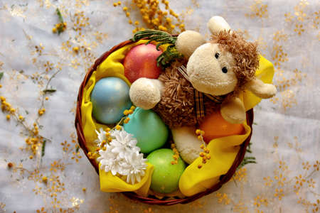 Easter lamb with colored pearly eggs in basket. Shallow depth of field
