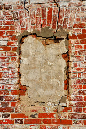 window opening: Wall of old orange shabby bricks with concreted window opening as background or texture. Vertical orientation