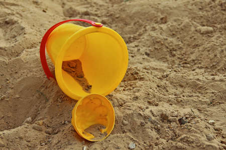 kiddie: Yellow childrens bucket and mold, lying in sandbox. Shallow depth of field