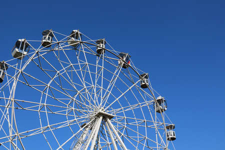 clear day: Ferris wheel against bright blue sky on clear day. Part of wheel on left
