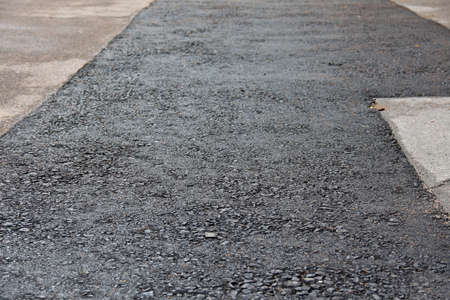 patched: Neatly patched asphalt in pavement. Shallow depth of field. Focus on bottom of frame