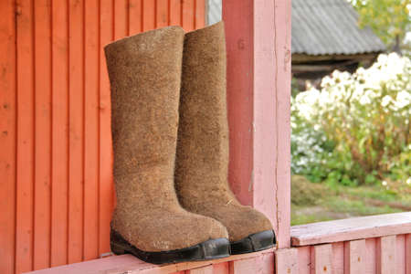 valenki: Durable rural russian high boots drying on balcony. Shallow depth of field, focus on left boots