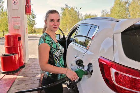 benzine: Young beautiful woman-motorist fills her car with benzine at gas station Stock Photo