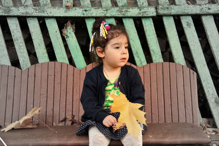 kiddie: Little girl sitting on bench with bouquet of autumn maple leaves. Gradient from black-white to colored tones Stock Photo