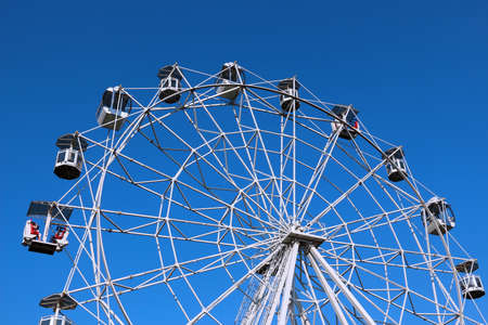 clear day: Ferris wheel against bright blue sky on clear day. Part of wheel