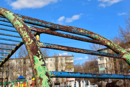 jungle gym: Rusty jungle gym with leafless paint at playground in bright sunny day on background of blue sky. Shallow DOF