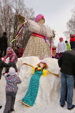 bugaboo: Children play in snow around scarecrow for festive holiday Maslenitsa, February 22, 2015, Tula, Russia