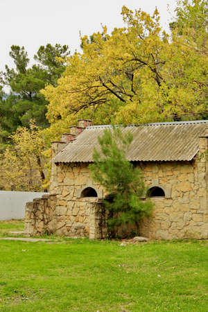 semicircular: Interesting stone house with small semicircular windows. Early autumn landscape