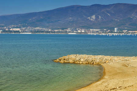 seafronts: Sea resort town of Gelendzhik in sunny day on Black sea coast. View on sandy beach and city center with mountains in background Stock Photo