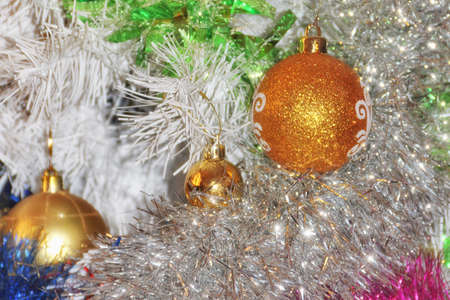Festive multi-colored postcard with sparkling Christmas tinsel and golden shining balls. Shallow depth of field
