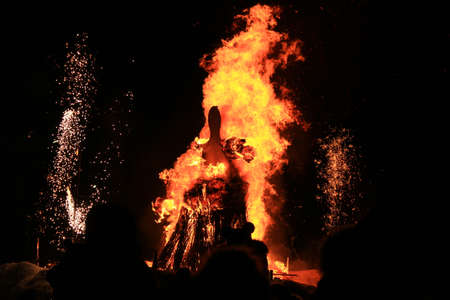 Traditional burning of Maslenitsa Scarecrow on seeing Russian winter on last day of Shrovetide in dark evening. Burning effigy on black background. Horizontal orientation